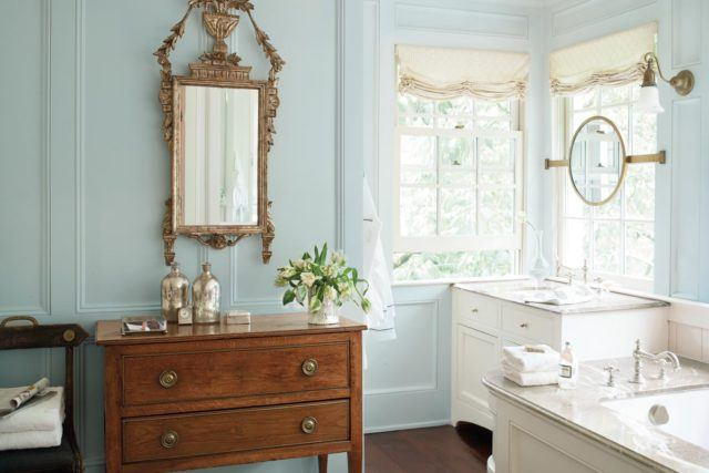 bathroom with light blue walls white vanities and a brown vanity