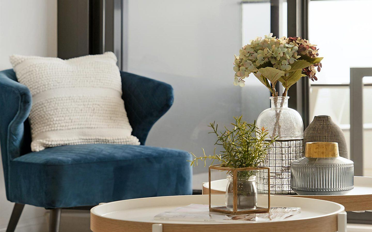 blue chair with white pillow behind circular brown tables with flower vases
