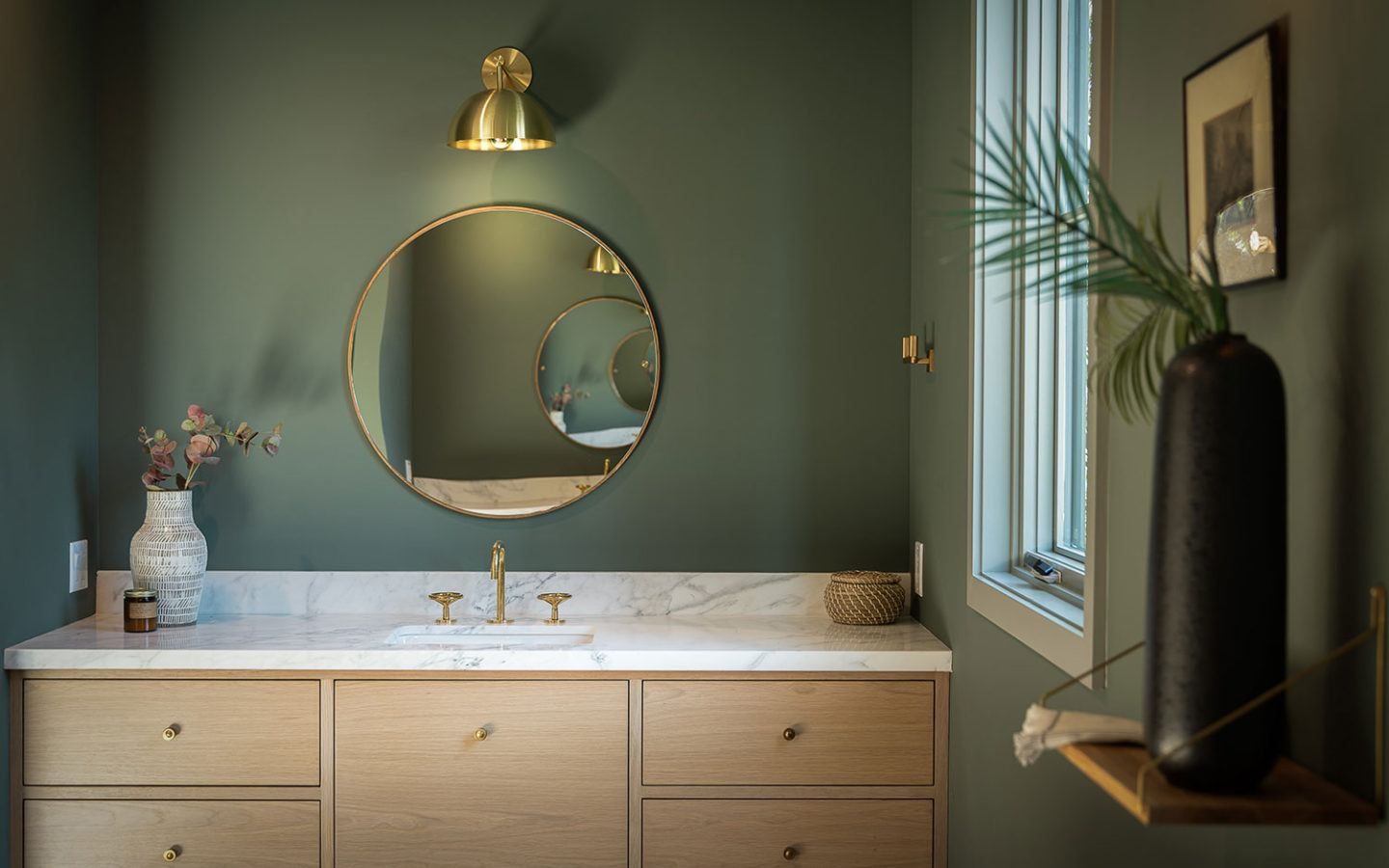 bathroom vanity with circular mirror and green walls