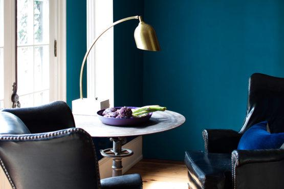 leather chairs and table with gold lamp in room with blue walls