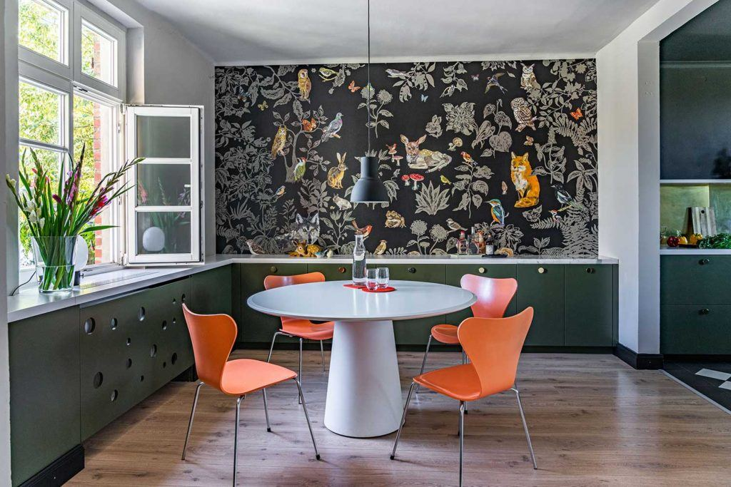 dining area with table surrounded by four orange chairs and wall with floral and animal wallpaper on it in the background