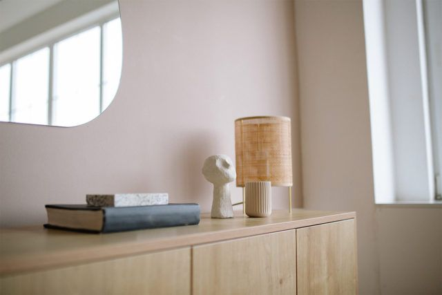 small dresser with book lamp and sculpture on it in front of pink wall and mirror