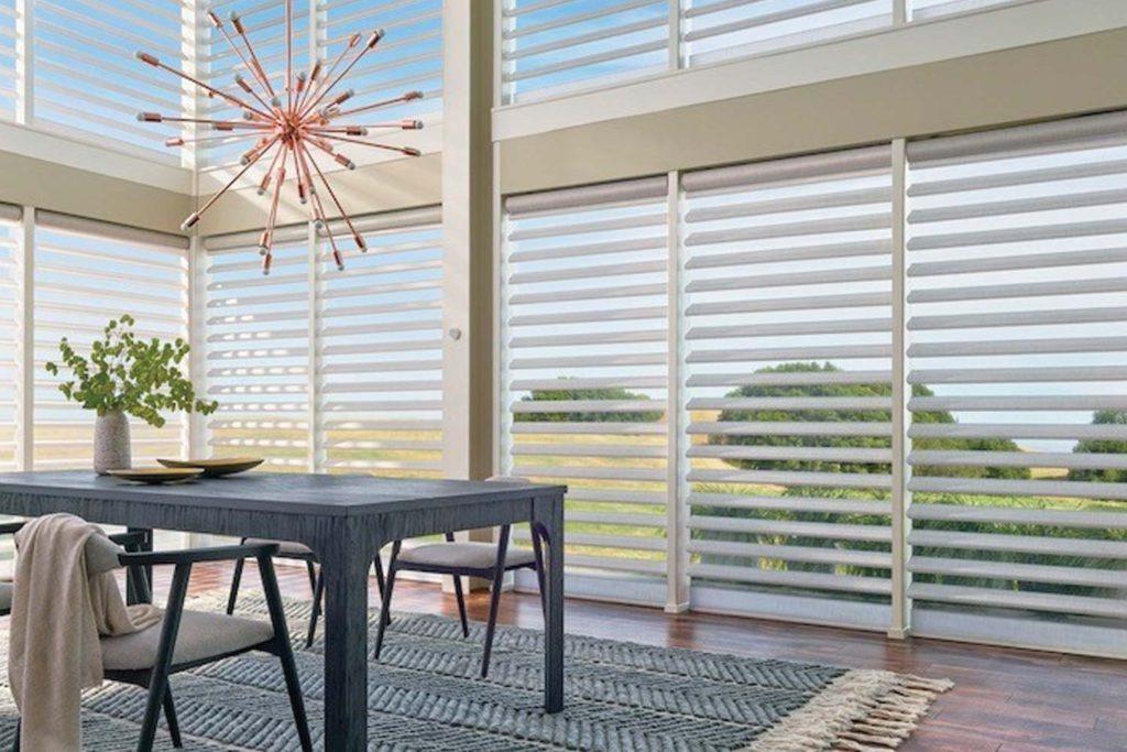 dining room with hunter douglas blinds on big windows