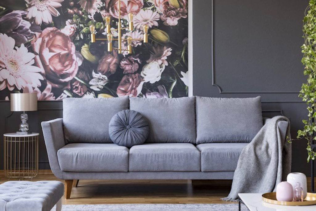 grey couch with circular cushion and blanket in front of wall with grey panel and floral wallpaper panel