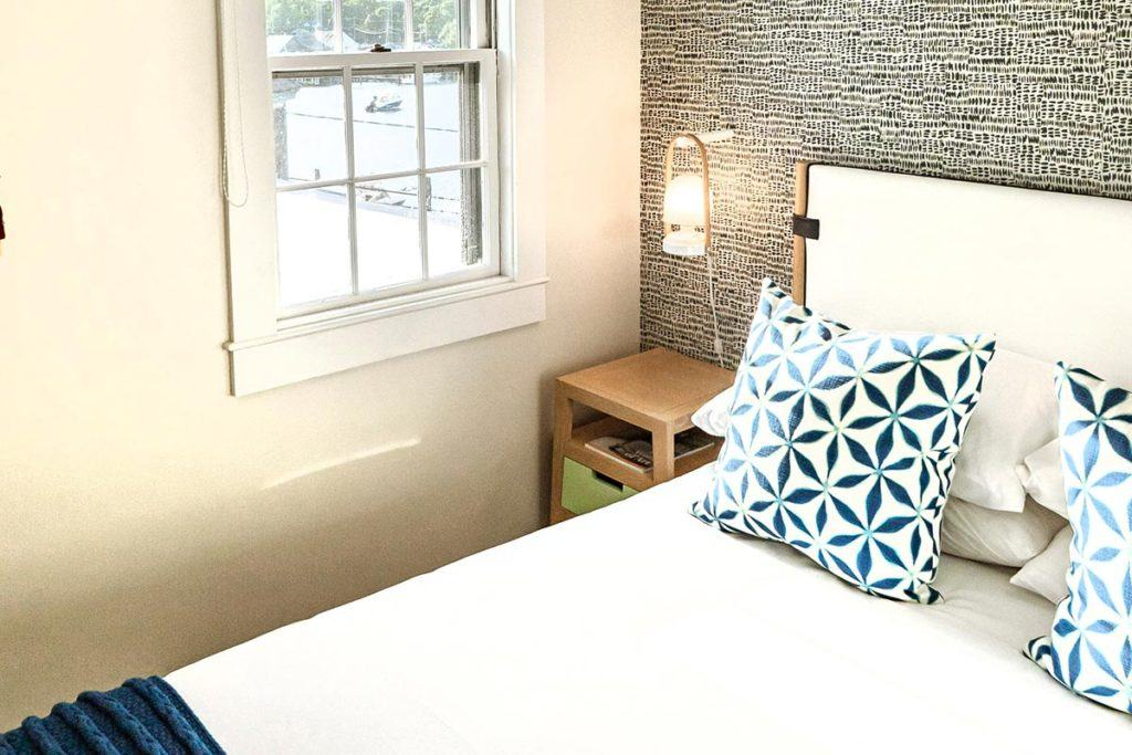 bed with blue pattern pillows in front of wall with black pattern wallpaper