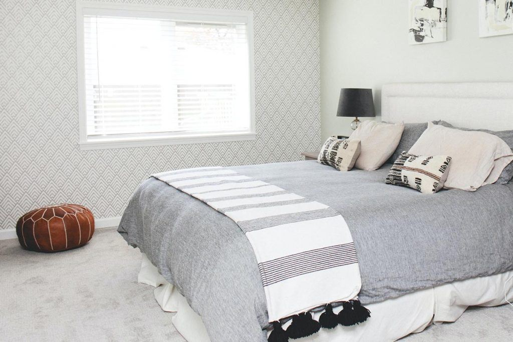 bedroom with orange brown pillow and bed with grey blanket