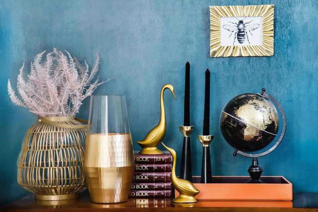 small globe books candles vases and more sitting on brown desk in front of blue wall with framed photo of bee illustration