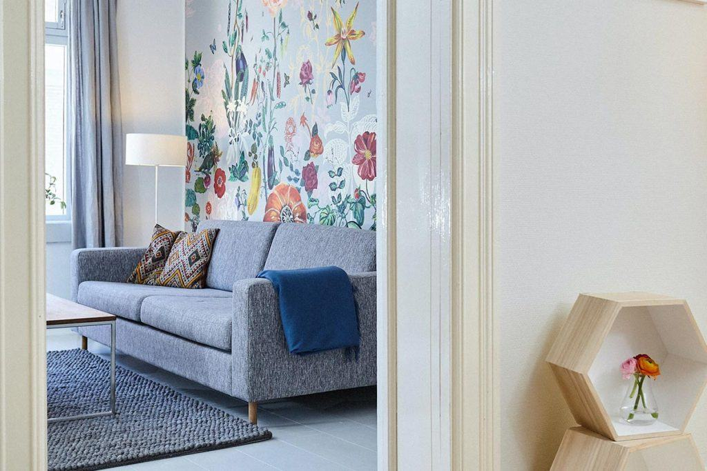 looking through entrance to room with grey couch and floral colorful wallpaper