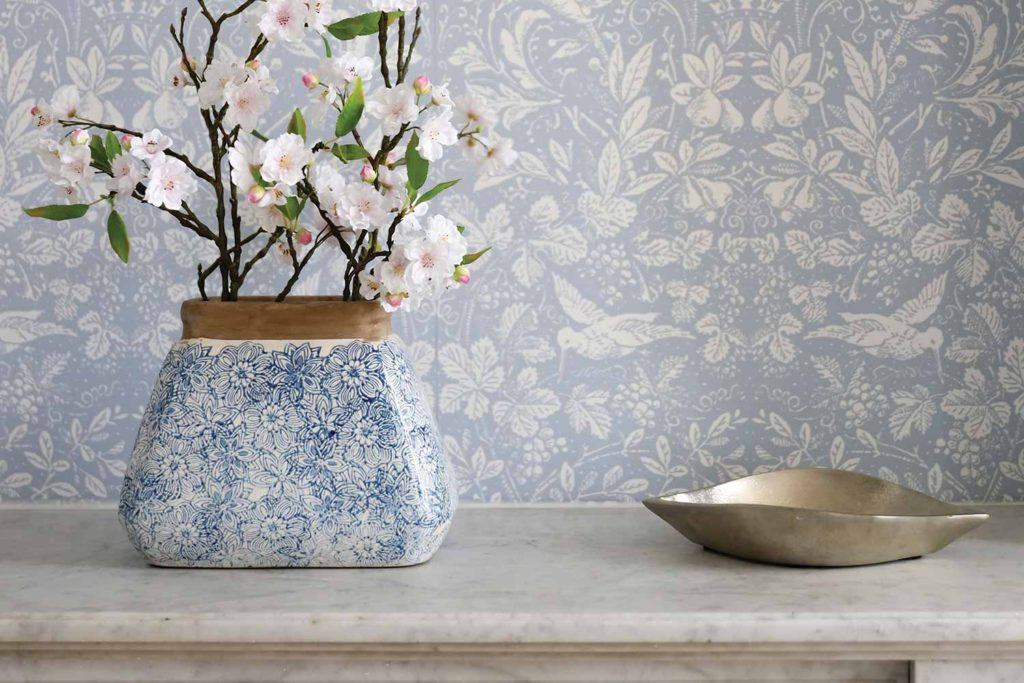 vase with blue floral pattern on marble table against wall with blue floral pattern wallpaper