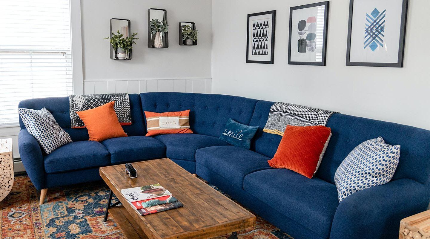 living room with white walls and long blue couch with orange and blue pillows